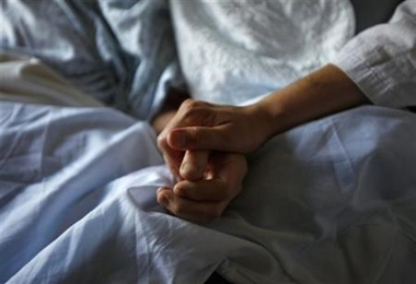 A woman holds the hand of her mother who is dying from cancer during her final hours at a palliative care hospital in Winnipeg, Canada (Reuters)